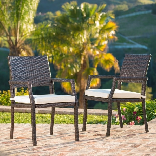 These wicker dining chairs are a great addition to any outdoor set. Featuring top quality wicker along with a cushioned water resistant fabric seat cushion, these chairs are both stylish and comfortable. Both light and durable, these chairs are ideal for any type of patio, especially if you love hosting.    Includes: Two (2) chair  Material: Wicker, powder coated iron  Cushion material: Weather resistant polyester fabric  Color: Multi-brown  Cushion color: White  Assembly required: Yes  Weight: 15-pounds  Dimensions: 34.25 inches high x 21 inches wide x 26 inches deep   Seat dimensions: 16 inches high x 18 inches wide x 17.75 inches deep  Armrest dimensions: 24.75 inches high     Assembly Required