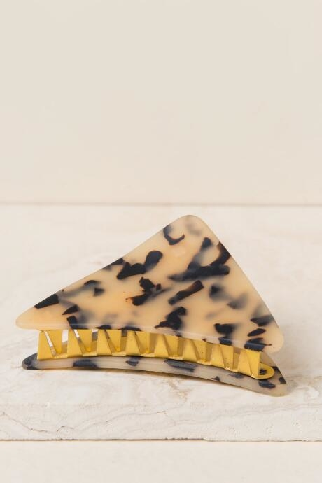 The Deryn Tortoise Claw Clip features a triangle design with a tortoise print and gold metal claw.