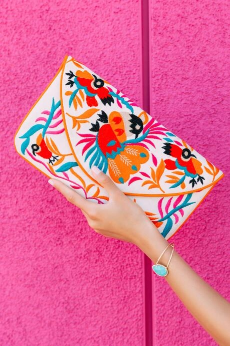 The Adrianna Bird Clutch Crossbody features a white envelope shaped clutch with embroidered birds in orange, red, turquoise, and pink thread.