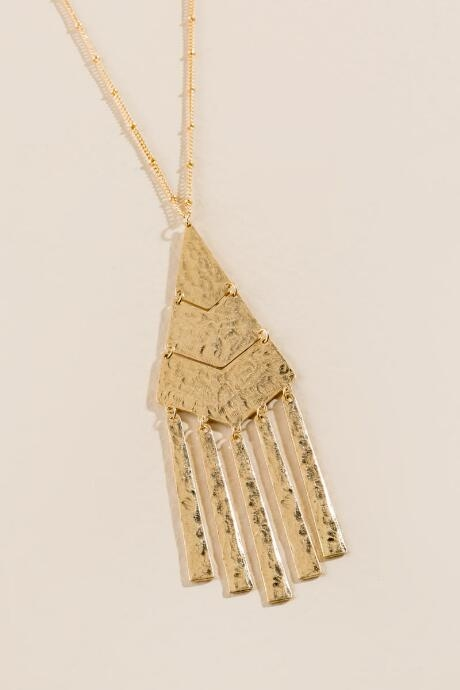The Ariel Hammered Metal Pendant Necklace is a long pendant necklace featuring hammered metal.