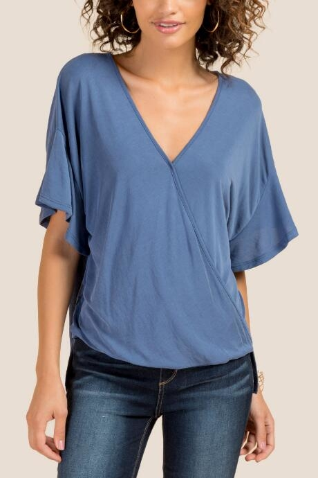 Avery Surplus Ruffle Sleeve Knit Top features a deep v-neck.