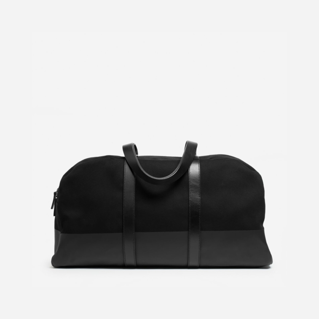 Our carry-on twill weekender bag has full-length leather straps and a contrast base that's screen printed 11 times for durability and protection against wet grass and dirty floors. Women's Twill Weekender Bag by Everlane in Black